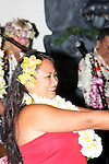 A female Hawaiian Dancer performing with the musical instruments played by the musicians