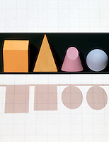 GEOMETRIC SOLIDS &amp; SHADOWS<br /> Cube, 4-Sided Pyramid, Truncated Cone &amp; Sphere<br /> Four wooden models stand on a narrow base, their 2-dimensional shadows fall on a grid foreground.
