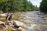Backcountry hiker crossing the East Branch of the Pemigewasset River in the Pemigewasset Wilderness of Lincoln, New Hampshire USA
