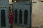A young girl watches from a gate as U.S. soldiers on Humvee patrol pass by her family's house in Samarra, Iraq. Soldiers with Company C, 2nd Battalion, 327th Infantry Regiment encounter hostile fire and IEDs almost daily in the city, but these photos were taken during a rare four-day period when no attacks occurred. Nov. 14, 2007. DREW BROWN/STARS AND STRIPES