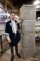 """Tokubee Masuda, CEO of the Tsukinokatsura sake brewery with a metal cage used to make """"nigori"""" cloudy sake. Fushimi, Kyoto, Japan, October 10, 2015. Tsukinokatsura Sake Brewery was founded in 1675 and has been run by 14 generations of the Masuda family. Based in the famous sake brewing region of Fushimi, Kyoto, it has a claim to be the first sake brewery ever to produce """"nigori"""" cloudy sake. It also brews and sells the oldest """"koshu"""" matured sake in Japan."""