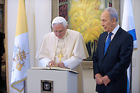 Pope Benedict XVI shakes hands with Israel's President Shimon Peres (R) during a welcoming ceremony on his behalf upon his arrival at Tel Aviv's Ben Gurion International airport May 11, 2009.