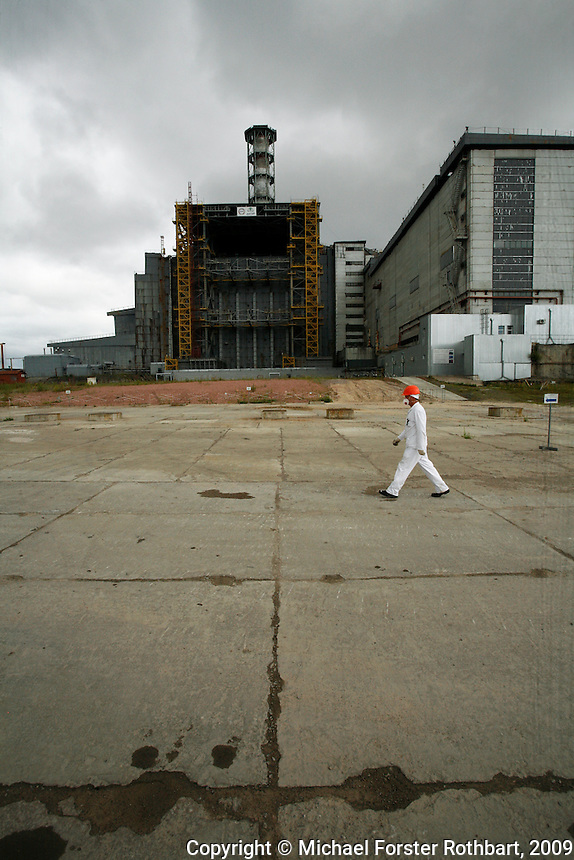 &ldquo;When I had a tooth extracted, I asked them to test it. They found 22 radioactive elements. Chernobyl is in us and we are in Chernobyl.&rdquo; &mdash; Sergei Koshelev, videographer for the Chernobyl Shelter Implementation Plan<br /> <br /> Sergei Koshelev crosses the high-radiation zone beside Chernobyl&rsquo;s ground zero. The concrete and lead Sarcophagus encloses the ruins of the reactor hall where the meltdown occurred. <br /> <br /> The Sarcophagus leaks and is structurally unstable. Construction workers preparing foundations for a replacement &ldquo;New Safe Confinement&rdquo; can hit their maximum daily dose in two to three hours.<br /> <br /> Sergei&rsquo;s wife Lyudmila also works at Chernobyl. &ldquo;We arrived here as young people,&rdquo; she says. &ldquo;Our life is here.&rdquo;<br /> <br /> ------------------- <br /> This photograph is part the book of Would You Stay?, by Michael Forster Rothbart, published by TED Books in 2013. The photos come from Forster Rothbart&rsquo;s two long-term documentary photography projects, After Chernobyl and After Fukushima.<br /> &copy; Michael Forster Rothbart 2007-2013.<br /> www.afterchernobyl.com<br /> www.mfrphoto.com &bull; 607-267-4893 &bull; 607-436-2856<br /> 34 Spruce St, Oneonta, NY 13820<br /> 86 Three Mile Pond Rd, Vassalboro, ME 04989<br /> info@mfrphoto.com<br /> Photo by: Michael Forster Rothbart<br /> Date:  7/2009    File#:  Canon 5D digital camera frame 72232<br /> ------------------- <br /> Original caption: <br /> Sergei Koshelev, videographer for the Chernobyl SIP PMU (Shelter Implementation Plan Project Management Unit) visits the high-radiation zone just west of the Chernobyl Nuclear Power Plant&rsquo;s 4th Block Shelter (also called the Sarcophagus). Workers refer to the area inside the final high-security perimeter as the &ldquo;local zone,&rdquo; where they are doing groundwork for construction of the New Safe Confinement super-structure that will replace the Sarcophagus.<br /> <br /> Th