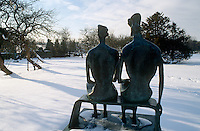 A bronze sculpture of a seated couple in bright sunlight against pristine winter snow