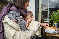 A mother breastfeeds her 15 month old boy who is in a sling and holding a piece of bread.<br /> <br /> London, England, UK<br /> 22-03-2015<br /> <br /> &copy; Paul Carter / wdiip.co.uk
