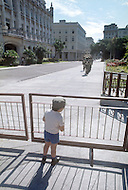 June, 1977. Havana, Cuba. Eighteen years after the Cuban Revolution the first U.S. tourists were permitted to visit Havana. Child watches the changing of the guards in front of the Museum of Revolution.