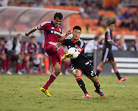 Long Tan (27) of D.C. United has the ball cleared away from him by Pavel Pardo (17) of the Chicago Fire at RFK Stadium in Washington, DC.  D.C. United defeated the Chicago Fire, 4-2.