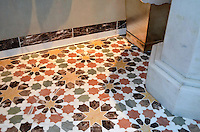 This custom bathroom floor features Granada Grande, a handmade mosaic shown in polished Emperador Dark, Verde Luna, Rosa Verona, Calacatta Tia and Giallo Reale, is part of the Miraflores Collection by Paul Schatz for New Ravenna.<br />