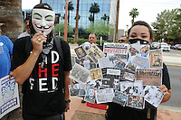 """Phoenix, Arizona (July 28, 2012) - About three hundred people marched to protest the second anniversary of the approval of some provisions of the SB 1070 immigration law. The march, called """"No Papers, No Fear"""" was organized by immigrant rights groups who say the law discriminates people of brown skin. In this photograph, two demonstrators show their opposition to police brutality during the """"No Papers No Fear"""" march in Phoenix, Arizona. The march took place two years after parts of the SB 1070 immigration laws were enacted. Photo by Eduardo Barraza © 2012"""