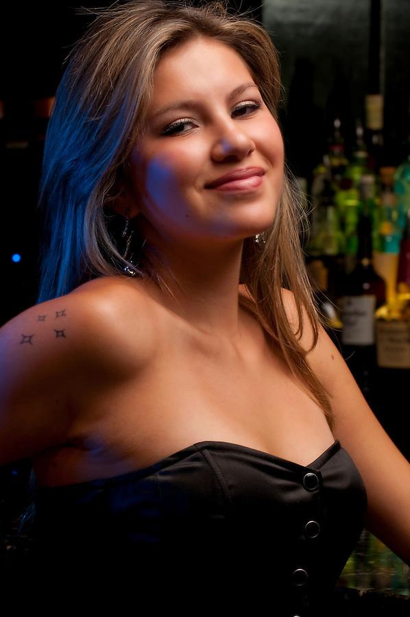 Young woman in a nightclub bar, posing very sexy.