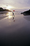 Cape Sebastian State Park Southern Oregon Coast young girl at sunset with rock formations at low tide running and flying kite Oregon State USA