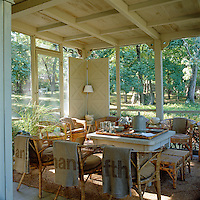 Wicker chairs surround a square table on this porch and blankets hang over the backs of the chairs for guests to keep warm on cool evenings