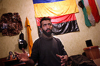 """UKRAINE, 02.2016, Novohrodivka, Oblast Donetsk. Ukrainian-Russian conflict concerning Eastern Ukraine / Foreign volunteers (""""Task Force Pluto"""") fighting with the far-right militia Pravyi Sektor against the Russian-backed separatists: Ben (Austria) gestures in his room, the wall behind him is full of memorabilia like the jacket of a fallen comrade, an Ukrainian flag, a Peshmerga flag from Iraq and a Right Sector flag (red-black) with a swastika on it. © Timo Vogt/EST&OST"""