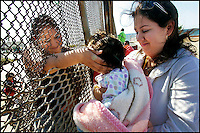 Left,  Jacqueline Huerta caresses her niece Yisell Martinez, while reaching through the border fence, while her Mom Rosalie Martinez holds her, at borderfield State Park.