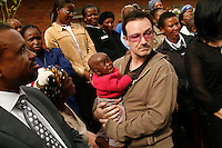 Bono, the lead singer of rock band U2, holds the child of a local HIV activist among those who have gathered to greet him at an HIV/AIDS clinic.  The clinic is run in the grounds of the town's hospital.