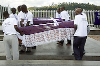 Rwanda. Southern province. Murambi. Genocide Memorial. Internment of Tutsis, killed during the 1994 genocide. A group of young black men from the Ibuka association ( Tutsi survivors of the 1994 Genocide) carry two coffins covered by mauve materials with a Holy Cross on top. Mauve is the color of mourning. Over 50'000 people perished on the site and thrown in mass graves. The site of Murambi is located in the district of Nyamagabe, in the former Gikongoro prefecture, Nyamagabe commune. © 2007 Didier Ruef