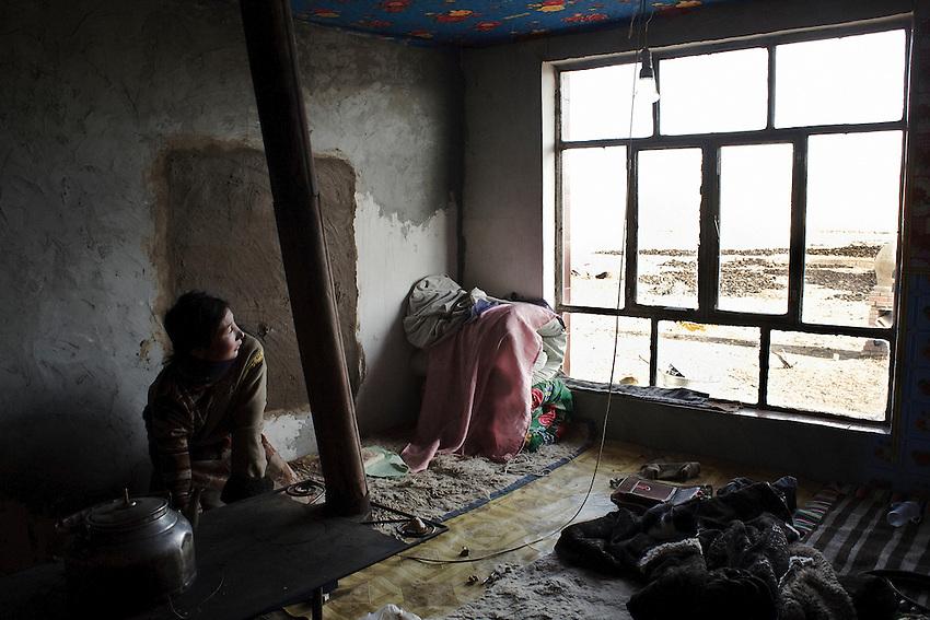 Dans sa pièce principale, AMu branche la batterie sur la lampe, ici allumée.