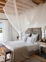 The white bedroom has a fresh and rustic feel with sheer curtains, simple white bedding and a mosquito net over the bed. The headboard is made from reclaimed wood attached to the wall.