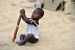 A child sits in the sand in Timbuktu, a city in northern Mali which was seized by Islamist fighters in 2012 and then liberated by French and Malian soldiers in early 2013. This child belongs to the Bella ethnic group, which has traditionally been exploited by the region's lighter-skinned groups.