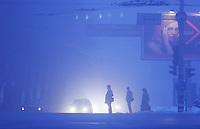 In the pre-dawn fog, commuters wait outside the Pechersk Metro station in Kyiv, Ukraine, 65 miles from Chernobyl. Radiation from Chernobyl dispersed erratically, based on winds and rainfall. Officially, the radiation leapfrogged over Kyiv and did not affect the capital. However, some Kyiv residents now question whether this is really true.  <br /> ------------------- <br /> This photograph is part of Michael Forster Rothbart's After Chernobyl documentary photography project.<br /> &copy; Michael Forster Rothbart 2007-2010.<br /> www.afterchernobyl.com<br /> www.mfrphoto.com <br /> 607-267-4893 o 607-432-5984<br /> 5 Draper St, Oneonta, NY 13820<br /> 86 Three Mile Pond Rd, Vassalboro, ME 04989<br /> info@mfrphoto.com<br /> Photo by: Michael Forster Rothbart<br /> Date:  2/2007    File#:  Canon 20D digital camera frame 8543 <br /> ------------------- <br /> Original caption: .Photo title:.Winter twilight in Pechersk, Kyiv..Caption:.In the pre-dawn fog, commuters wait to cross the street outside the Pechersk Metro station in Kyiv, 65 miles from Chernobyl...Radiation from Chernobyl dispersed erratically, based on winds and rainfall. Officially, the radiation leapfrogged over Kyiv and did not affect the capital. However, many Kyiv residents question whether this is really true. ..Quote: none.-------------------.