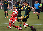 Jun 6, 2015; Portland, OR, USA; New England Revolution midfielder Kelyn Rowe (11) puts a shot on goal as Portland Timbers defender Liam Ridgewell (24) defends during the first half of the game at Providence Park. Mandatory Credit: Steve Dykes-USA TODAY Sports