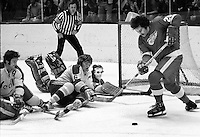 Seals Rick Smith, Bobby Stewart and goalie Gilles Meloche fend off Mickey Redmond.(photo copyright Ron Riesterer)
