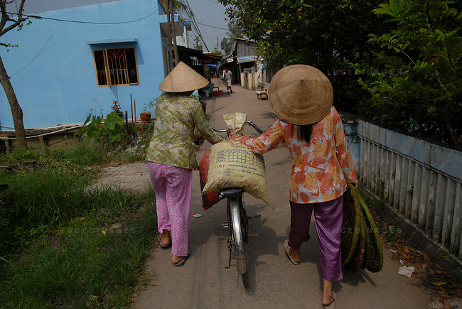 Vietnamese women transport supplies back to their village in Can Tho, Vietnam.