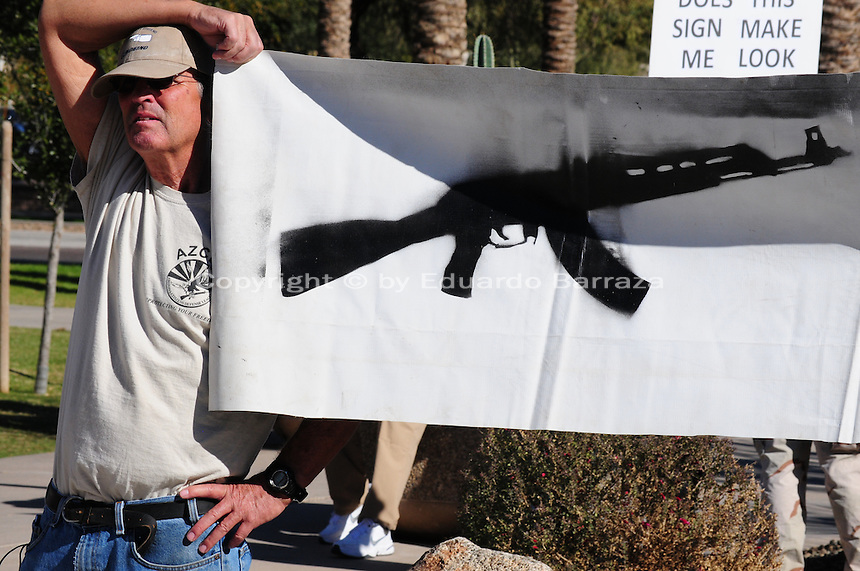 """Phoenix, Arizona. January 19, 2013 - A demonstrator holds a banner during Saturday's rally in Phoenix to oppose to proposed changes in gun control laws. As President Barack Obama proposed new gun regulations last week, gun owners demonstrated against it with national """"Guns Across America"""" rallies to defend the Second Amendment. Dozens showed up at the Arizona State Capitol, many of them carrying weapons. Photo by Eduardo Barraza © 2013"""