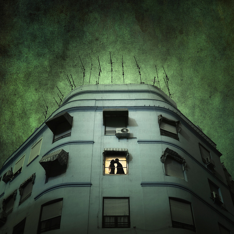 The silhouette of a man and woman kissing in a window of a large building with tv ariels on the roof