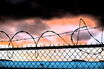Farmingdale, New York, USA. November 26, 2016.  Sunset in truck parking area in industrial storage area of Farmingdale in Long Island. Barbed wire tops chain link fence separating properties.
