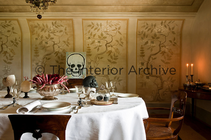 In the dining room a laid table with an unusual centrepiece made with beans and roses and a skull