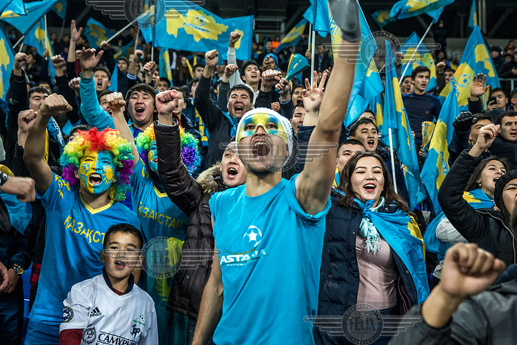 FC Astana fans sing during the club's Europa league game against Greek side Olympiacos, in the Astana Arena.