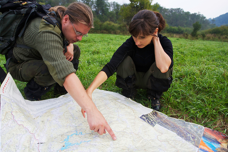 European bison or Wisent (Bison bonasus) researchers, Aleksandra Woloszyn-Galeza and Maciej Januszczak from the Carpathian Wildlife Research Station (Stacja Karpacka) showing the territories of two main bison herds in Bieszczady National Park on a map. San River, Krywe Nature Reserve, Bieszczady region, Poland.
