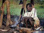 Natalin Konga cooks breakfast for her family in Pisak, a village in Southern Sudan. Konga is a United Methodist. NOTE: In July 2011 Southern Sudan became the independent country of South Sudan.