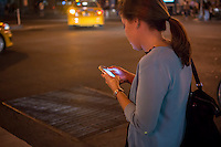 Young woman checks her smartphone in the trendy Meatpacking District of New York on Tuesday, August 20, 2013. © Richard B. Levine)