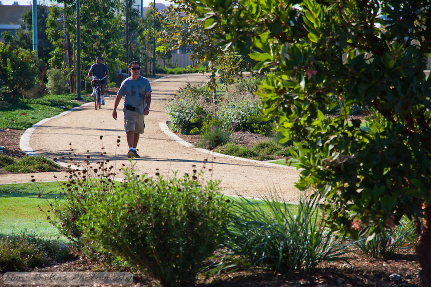 A walker and bicyclist use the walking path at Stanton Central Park one morning, framed by plants in the butterfly garden.