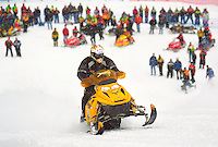 A MAN RIDES A SNOWMOBILE UP MARQUETTE MOUNTAIN SKI HILL IN MARQUETTE, MICHIGAN DURING A RACING EVENT AS PARTICIPANTS AND COMPETITORS LOOK ON FROM BELOW.
