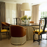 Antique Chinese chairs and contemporary armchairs are both found around the table in this dining room