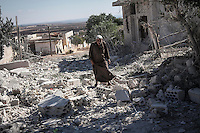 In this Wednesday, Sep. 25, 2013 photo, a Syrian man walks among the debris of destroyed residential buildings minutes after an airstrike hit Habit village, in the Syrian central province of Hama. (AP Photo)