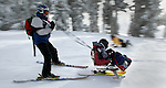 February 07, 2004 - (LtoR) Brian Andrews tethers Brittany Peterson of Salem, 8,  as she leads down the hill on a bi ski. The Shriner Hospital's Ski and Snowboard program pairs volunteers with disabled kids at  Timberline on Mt. Hood....KEYWORDS: skiers, children