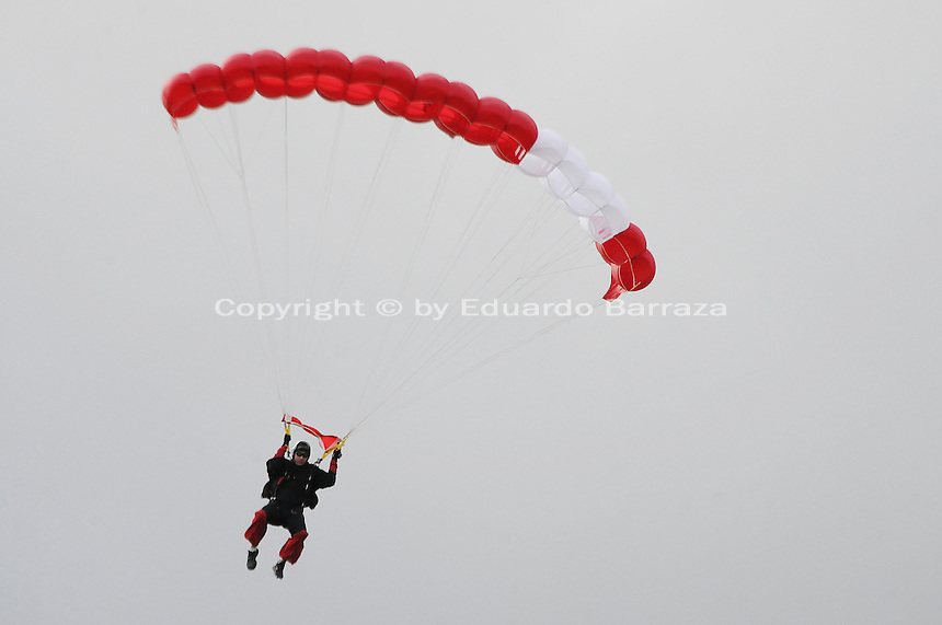 """Scottsdale, Arizona - A skydiver is seen in this photograph taking part in a swooping competition on April 9, 2011. He was part of a team of aerial performers who jumped from a helicopter and tried landing at a marked point on the ground. These """"canopy pilots"""" leveled off and navigated a course in front of spectators. The event was a """"swooping,"""" which consists of competitive parachuting where skydivers -also known as """"canopy pilots""""- try to touch down at a ground mark to win. Photo by Eduardo Barraza © 2011"""
