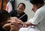 Nakorn Chai Sri, Thailand, March 2, 2012, Wat Bang Phra Tattoo Master gives a devotee a sak yant magical tattoo.