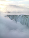 Niagara Falls covered in thick white mist, Canadian Horseshoe, beautiful sunrise scenery in soft light pastel colors, wintertime scenic. Niagara Falls, Ontario, Canada.