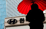 A woman holding an umbrella walks past an outdoor sign for Hyundai Motors in Seoul, South Korea.