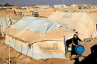 A woman empties a basin of water outside her tent at the  Zaatari Refugee Camp. Approximately two million people have fled the conflict in Syria. At least 130,000 of them live in Zaatari Refugee Camp, although it was designed to house 60,000, and a further 2,000 people arrive each day.