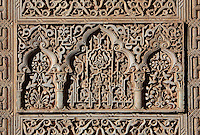 Section of intricately carved stucco wall with chain designs, floral decoration and stylised Arabic script, in the Court of the Lions, built 1362 in the second reign of Muhammad V, in the Nasrid dynasty Palace of the Lions, Alhambra Palace, Granada, Andalusia, Southern Spain. The Alhambra was begun in the 11th century as a castle, and in the 13th and 14th centuries served as the royal palace of the Nasrid sultans. The huge complex contains the Alcazaba, Nasrid palaces, gardens and Generalife. Picture by Manuel Cohen