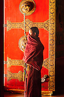 A monk strikes a contemplative pose in the doorway of the Maitreya temple of Tashilhunpo monastary in Tibet