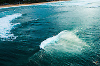 An aerial image of surfers catching a huge wave on the North Shore of O'ahu.