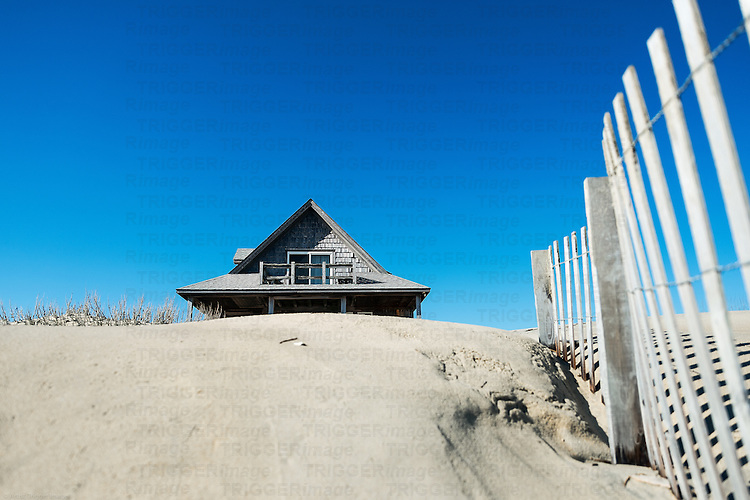 Secluded beach house with sand dunes and fence