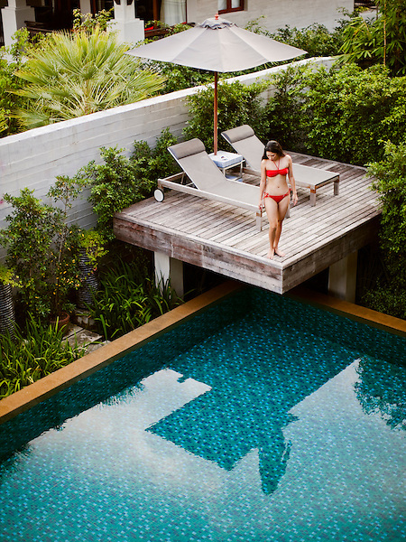Woman in Private Pool Villa at Indigo Pearl, Phuket, Thailand. A woman lounges by the pool of the Bensley Suite, a two-storey deluxe private pool villa at Indigo Pearl resort. Phuket, Thailand.